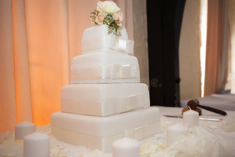 Biały ślubny tort z kwiatami dekoruje wierzchołek obrazy royalty free