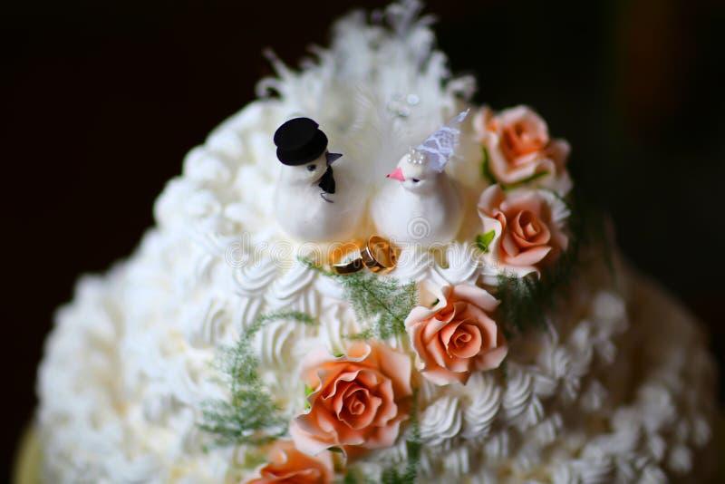 Biały śmietankowy ślubny tort z gołębiami i obrączkami ślubnymi dekorował z różami obrazy royalty free