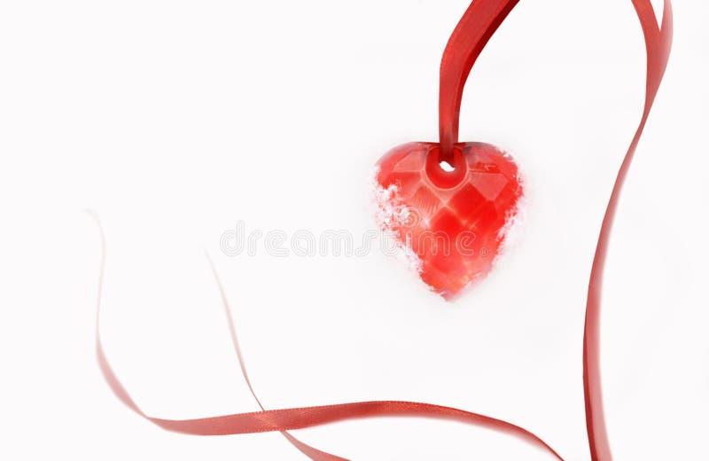 Biały śnieżny tło z czerwonym sercem na atłasowym faborku niezrównoważenie zdjęcia stock