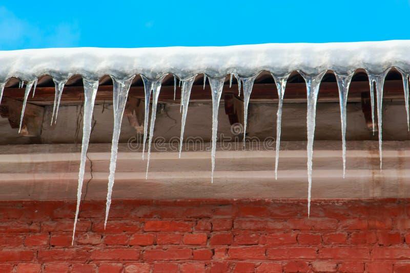 Biały śnieg na dachu dom wiesza od łupkowego dachu czerwonej cegły sople i obrazy royalty free