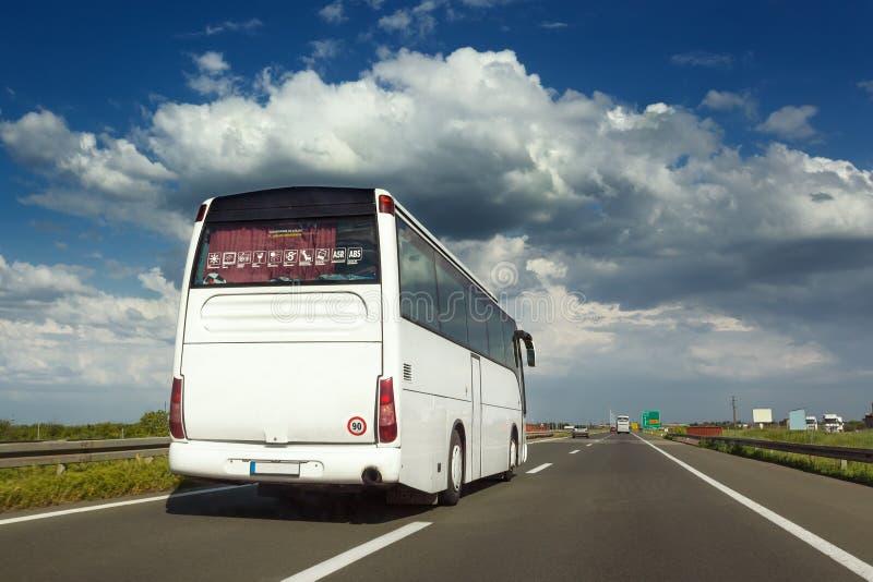 Biały autobus jest robić dogonieniem na autostradzie obrazy royalty free