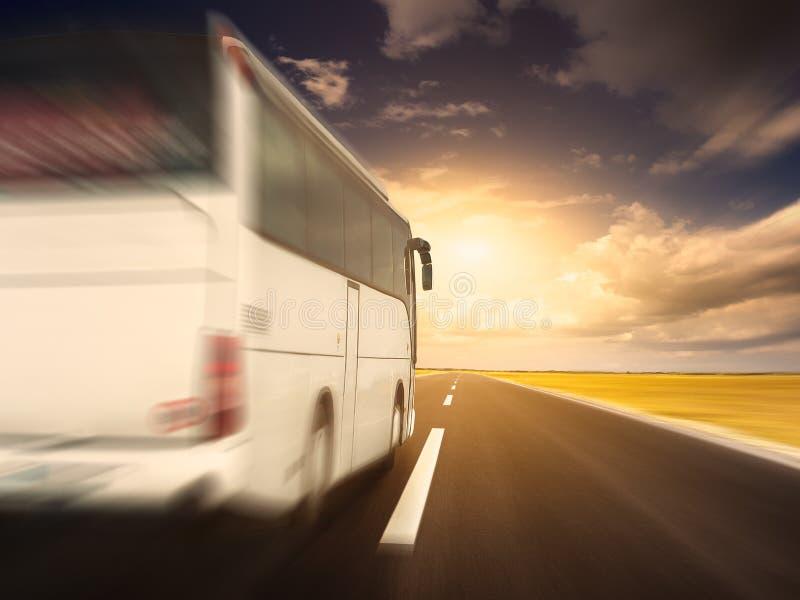 Biały autobus w szybkim jeżdżeniu na pustej asfaltowej drodze fotografia royalty free