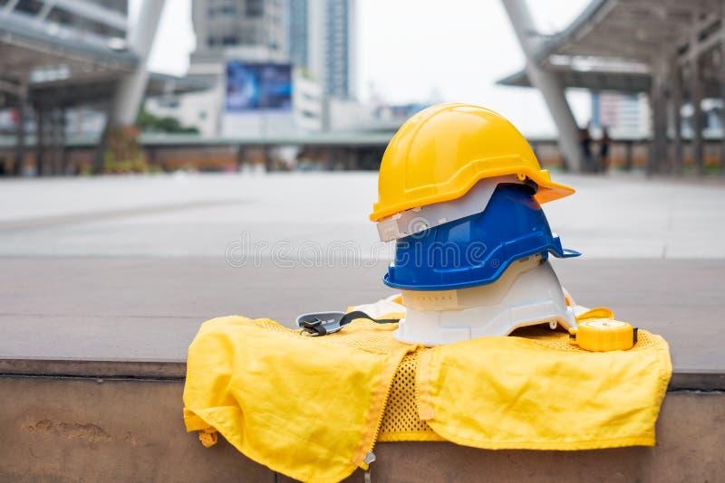 Biały, błękitny i żółty zbawczy ciężki hełm z formalny kamizelkowym dla przemysłowego bezpieczeństwa robociarza, fotografia royalty free