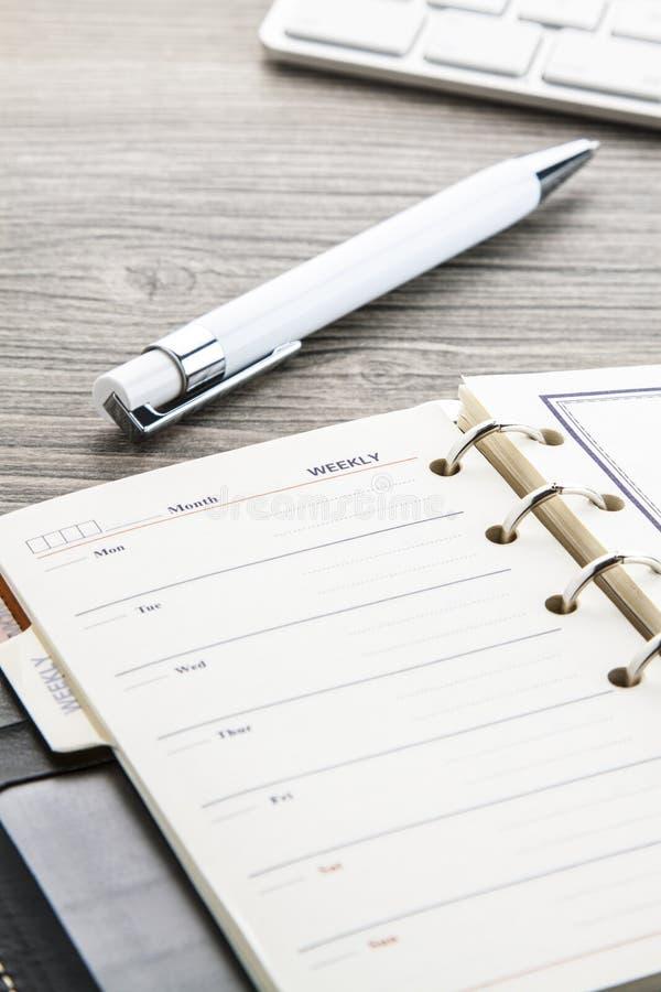 Biały ballpoint pióro i rzemienny tygodniowy kalendarz obraz royalty free