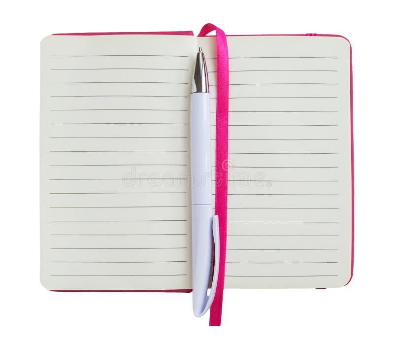 Biały ballpoint pióro na rozpieczętowanym notatniku z prążkowanym papierem w różowej pokrywie odizolowywającej na białej tło kopi obraz stock