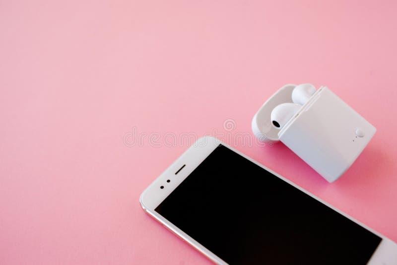 Biały bezprzewodowy smartphone i hełmofony kłamają na jaskrawym różowym tle Hełmofony w ładuje skrzynce obraz stock