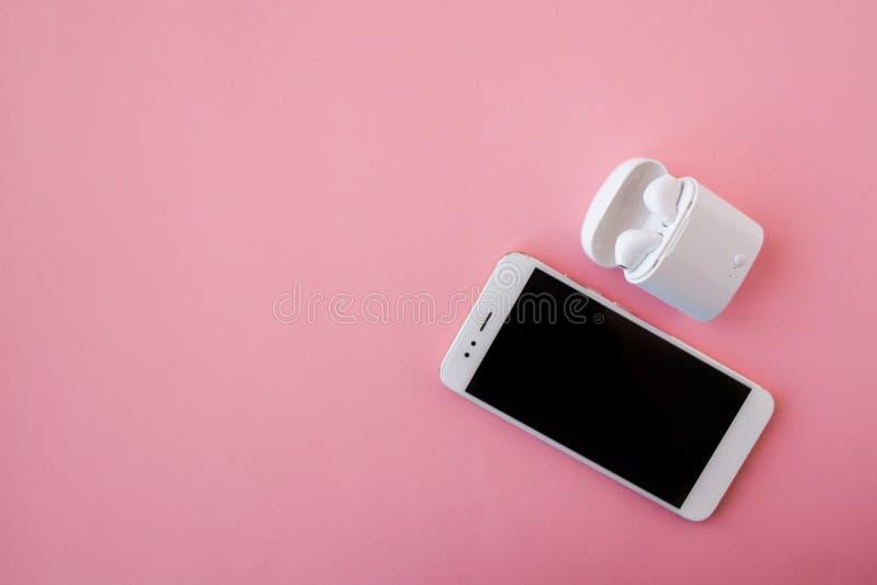 Biały bezprzewodowy smartphone i hełmofony kłamają na jaskrawym różowym tle Hełmofony w ładuje skrzynce obrazy stock
