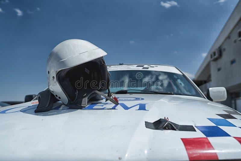 Biały bieżnego samochodu i hełma słoneczny dzień przed rasą zdjęcia stock