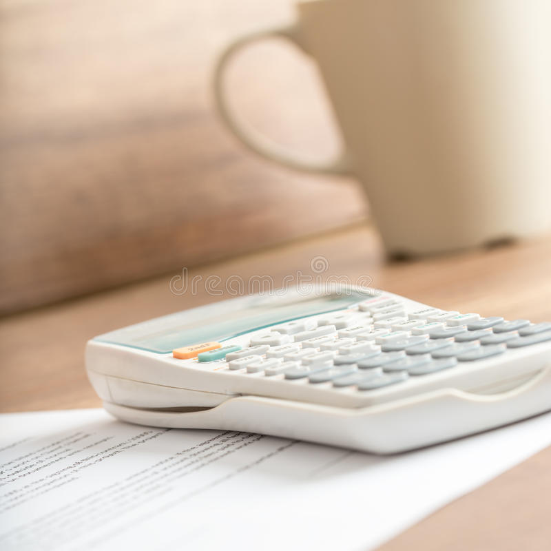 Biały biurko kalkulator na dokumencie obok kubka obraz royalty free