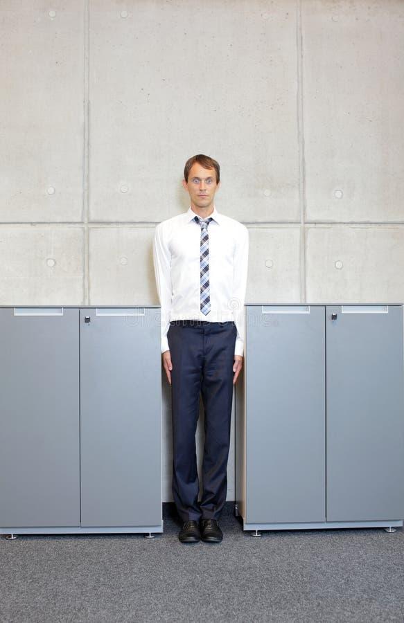 Biały biznesowego mężczyzna standng prosto między gabinetami w biurze zdjęcia royalty free