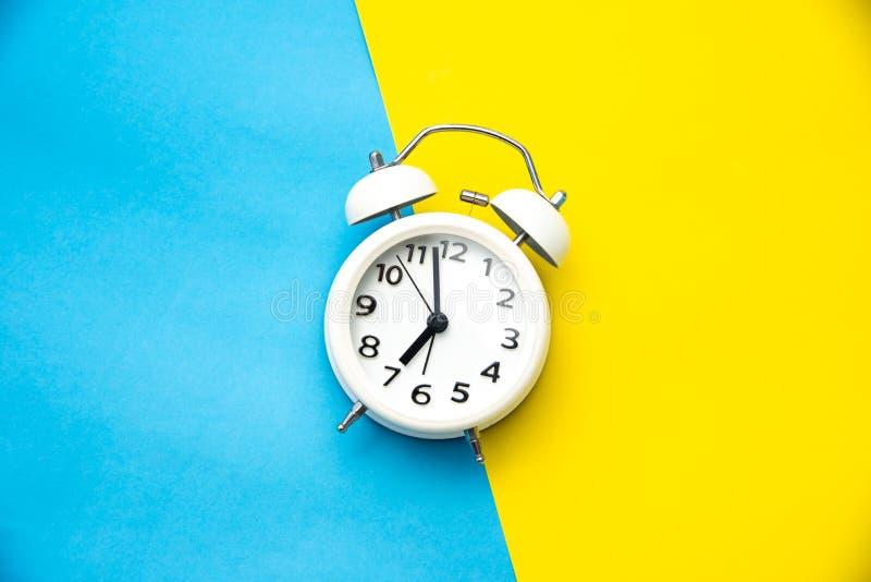 biały budzik na dwa brzmienia koloru kolorze żółtym i bławym backgr obraz stock