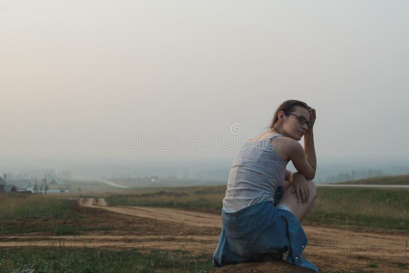 Biały caucasian młodej kobiety obsiadanie w wzgórzu blisko drogi obraz royalty free