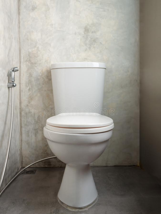 Biały ceramiczny Toaletowy puchar z zamkniętym toaletowym pokrywkowym siedzeniem i bidet brać prysznić w popielatej betonowej ści zdjęcia royalty free