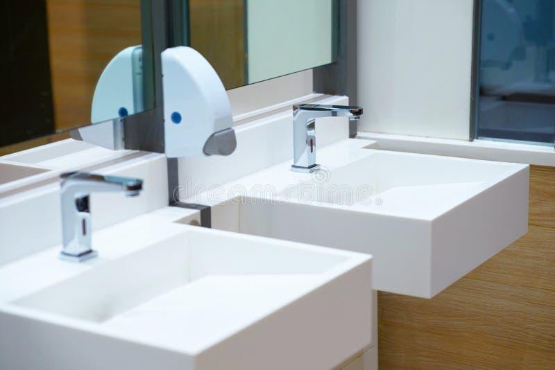 Biały ceramiczny zlew i wodny klepnięcie z mydlaną aptekarką w kąpielowym roo fotografia royalty free