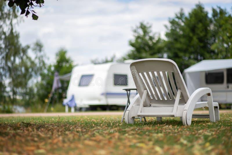 Biały deckchair w łące przy campsite zdjęcie stock