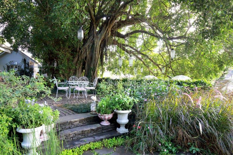 Biały dokonanego żelaza krzesło i stół w ogródzie w ranku fotografia stock