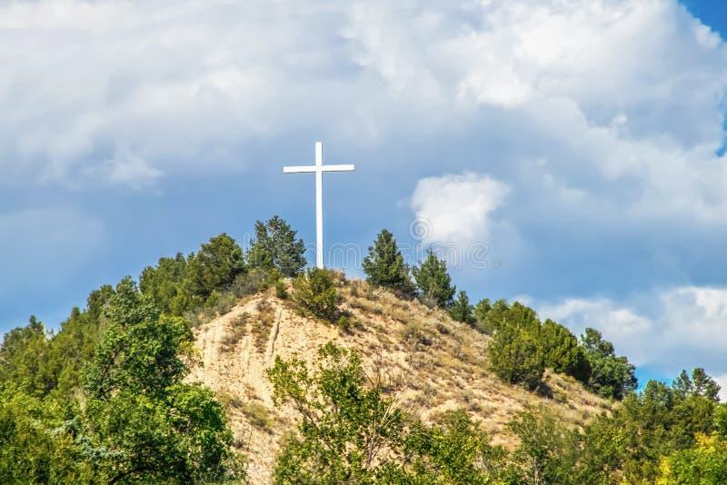Biały drewniany chrześcijanina krzyż na górze góry przeciw burzowemu niebu fotografia royalty free