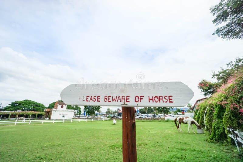 Biały drewniany kierunkowskaz z handwriting ono wystrzegać się koń przy zielonym jarda gospodarstwem rolnym fotografia royalty free