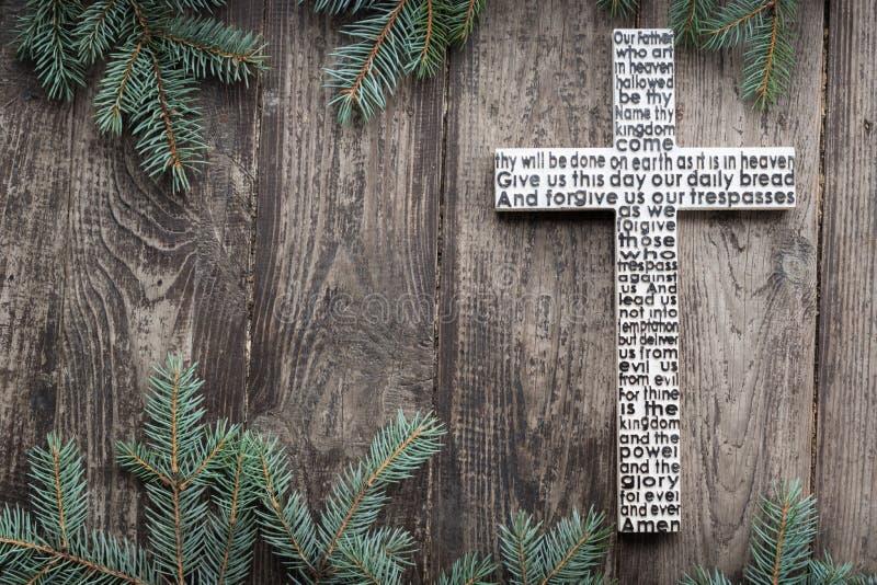 Biały drewniany krzyż z władyki modlitwą na podławej ciemnej drewnianej desce z jedlinowym gałąź tłem obrazy stock