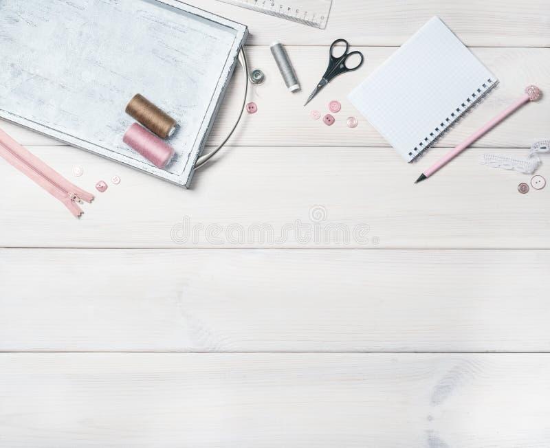 Biały drewniany tło z przedmiotami dla szyć Nici, suwaczek, guziki, nożyce, notatnik i ołówek, zdjęcie royalty free