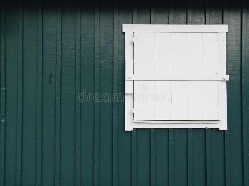 Biały drzwi na zielonej drewno ścianie fotografia royalty free