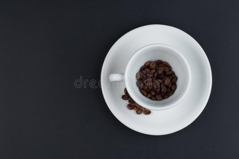 Biały filiżanka kawy i kawowe fasole odizolowywający na czarnym tle zdjęcie royalty free