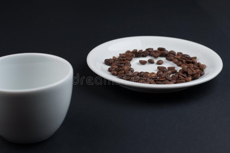 Biały filiżanka kawy i kawowe fasole odizolowywający na czarnym tle zdjęcia stock