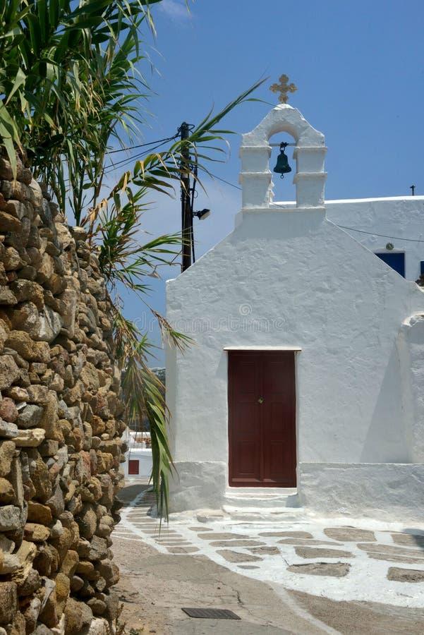 Biały grecki kościół z dzwonkowy wierza blisko kamiennej ściany z bambusową rośliną fotografia stock