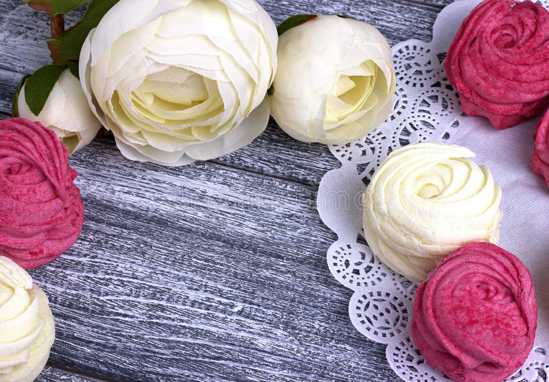 Biały jaskier kwitnie ranunculus białych i różowych zephyr marshmallows koronkową papierową pieluchę na szarym drewnianym tle kos fotografia stock