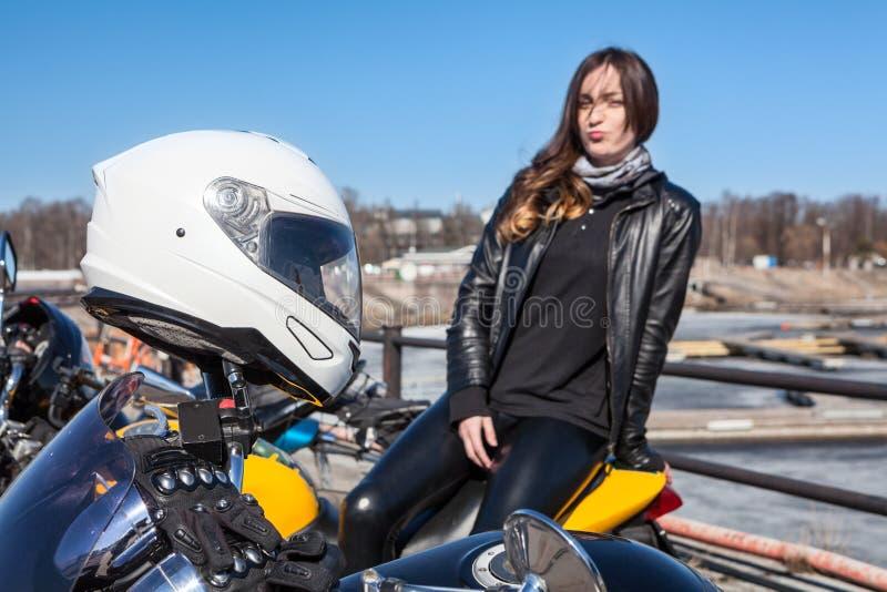 Biały kask ratunkowy na kierownicy motocykli i kobieta pasażer nieskoncentrowana na tle obrazy royalty free