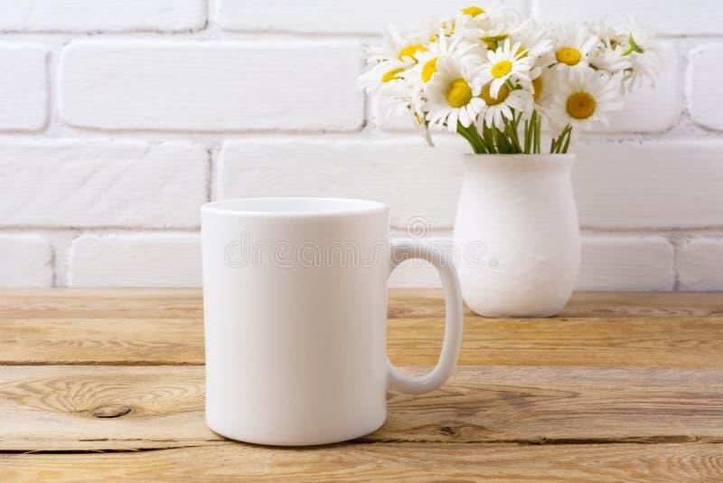 Biały kawowego kubka mockup z chamomile bukietem w nieociosanej wazie obraz stock