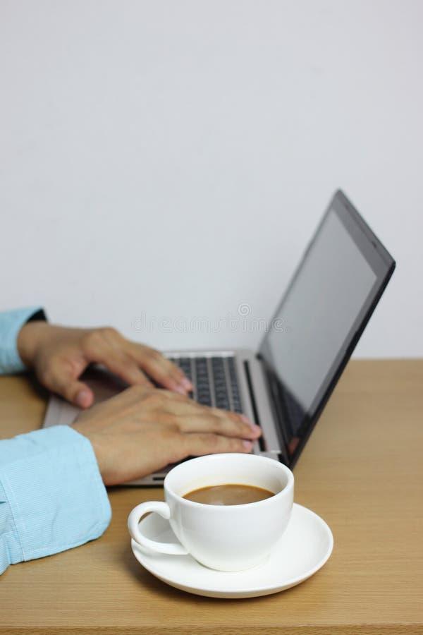 biały kawowy kubek na brąz drewnianej podłodze i komputeru laptopie brzęczenia obraz royalty free