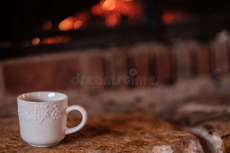Biały kawowy kubek na hearth obraz stock