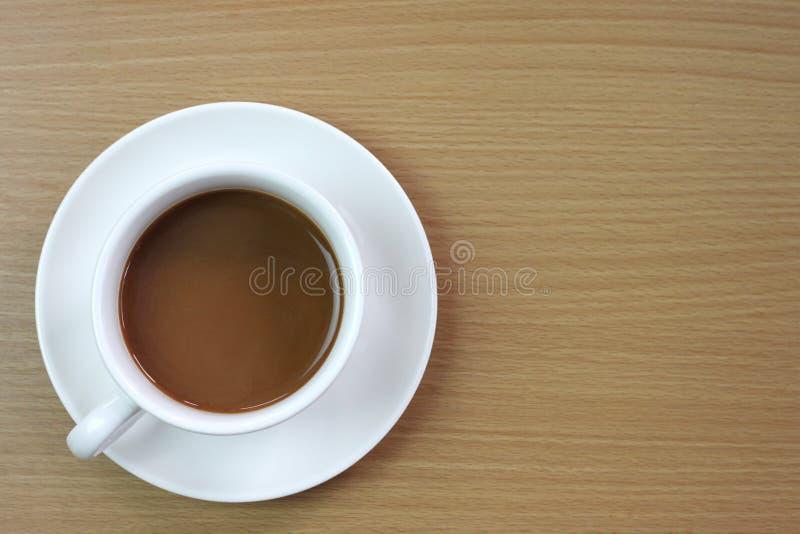 biały kawowy kubek umieszczający na brązu drewnianym stole zdjęcie stock