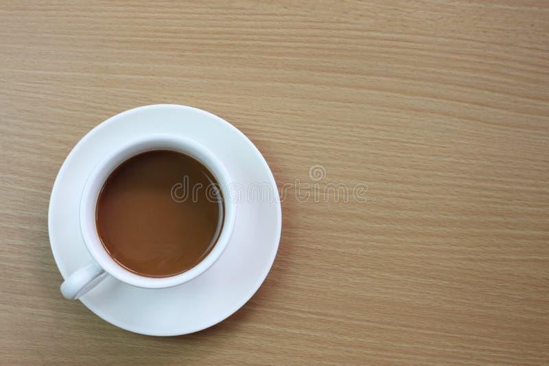 biały kawowy kubek umieszczający na brązu drewnianym stole obraz royalty free