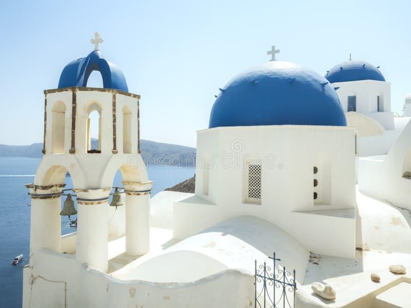 Biały kościół z dzwonami i błękitna kopuła przy Oia, Santorini, Greckie wyspy zdjęcia stock