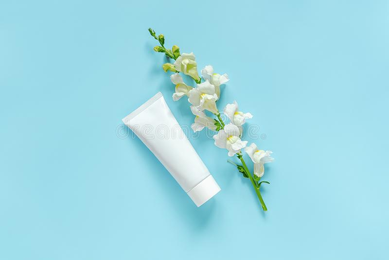 Biały kosmetyk, kwiat, medyczna biała tubka dla śmietanki, maść, pasta do zębów lub inny produkt na błękitnym tle i, zdjęcie royalty free