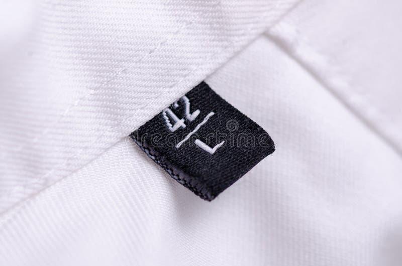 Biały koszulowy makro- etykietka rozmiar L obraz stock