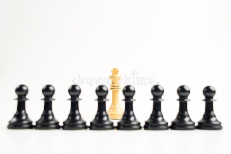 Biały królewiątko przed czarnymi pionkami fotografia royalty free