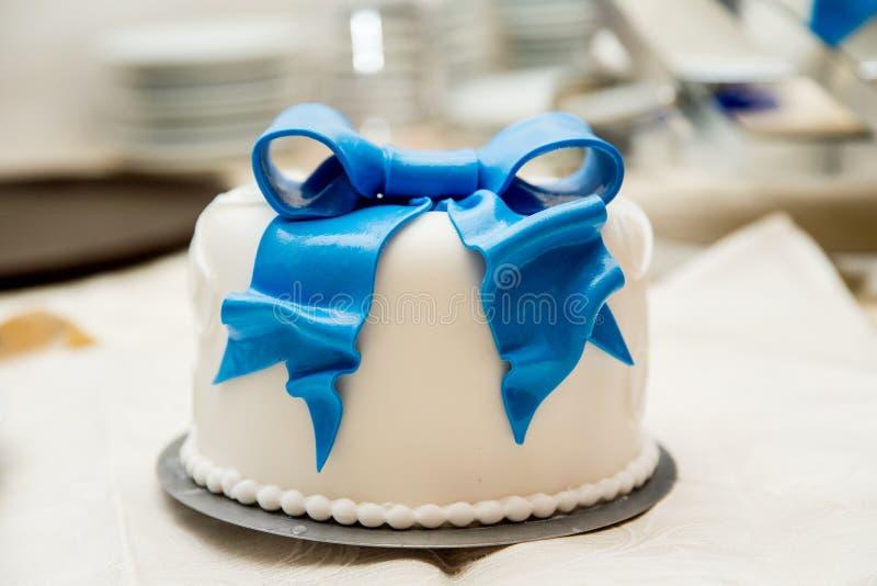 Biały kremowy kulebiak dekoruje z błękitnym łękiem fotografia stock