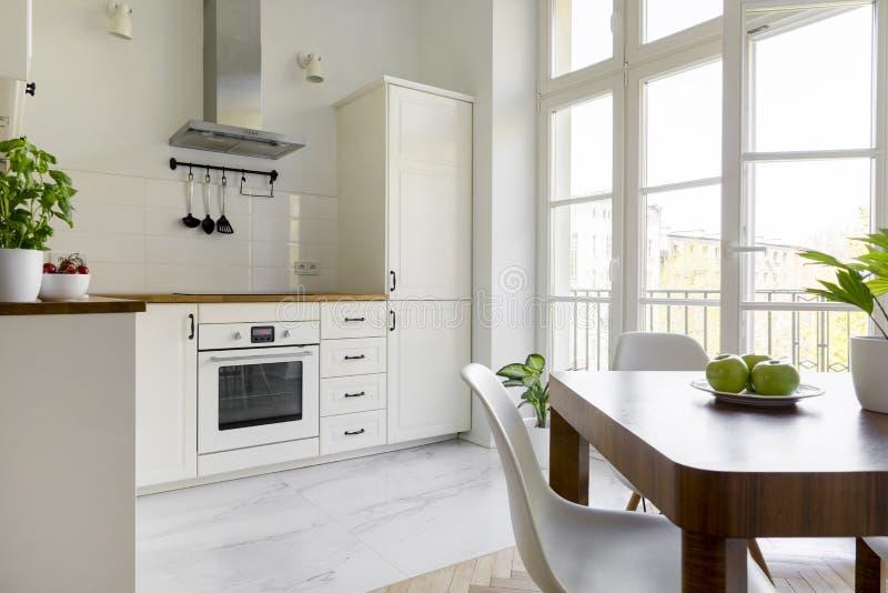 Biały krzesło przy drewnianym łomota stołem w prostych kuchennych wnętrzy wi zdjęcie royalty free