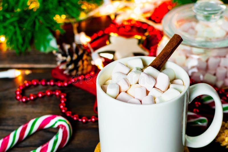 Biały kubek kakao z marshmallows, lizakami, jedlinowymi rożkami, choinki gałąź, girlandą i płatek śniegu na drewnianym stole, obrazy stock