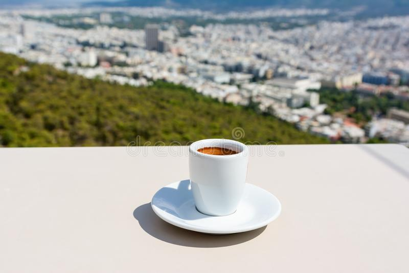 Biały kubek kawy espresso i widok miasta Aten na tle zdjęcia stock