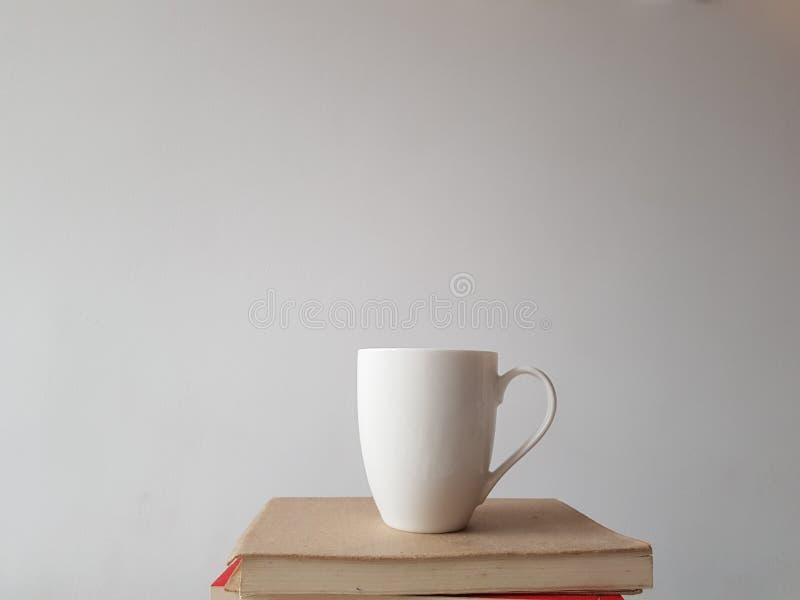 Biały kubek na białym tle, stoi na stosie książki fotografia stock