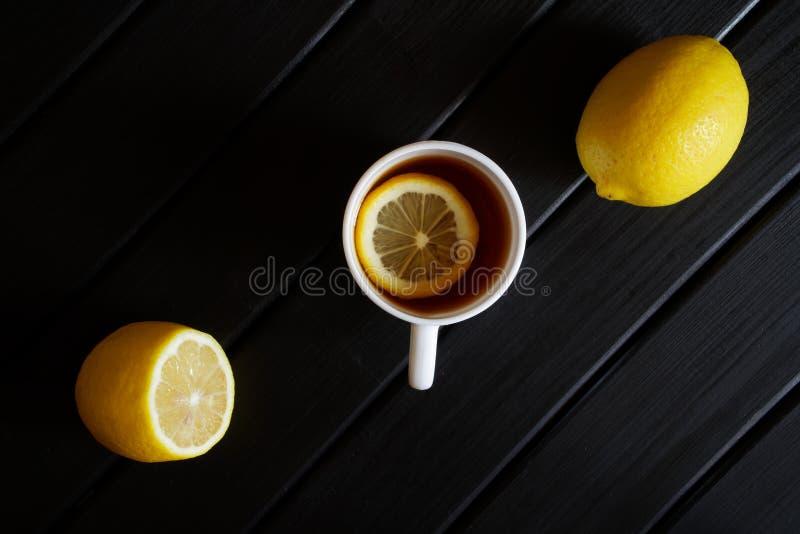 Biały kubek z czarną herbatą i cytryną na ciemnej drewnianej powierzchni na widok minimalista zdjęcia stock