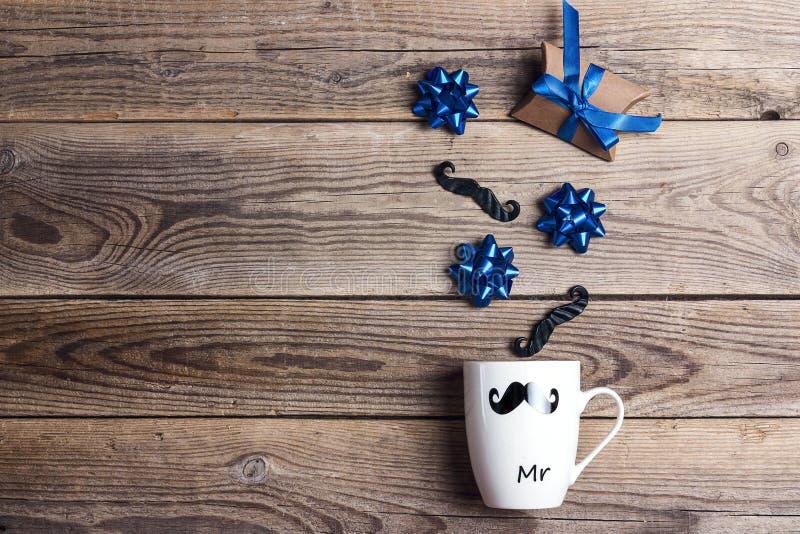 Biały kubek z dekoracyjnym wąsy, łękami i prezentem na drewnianym tle, Ojca dnia poj?cie zdjęcie stock