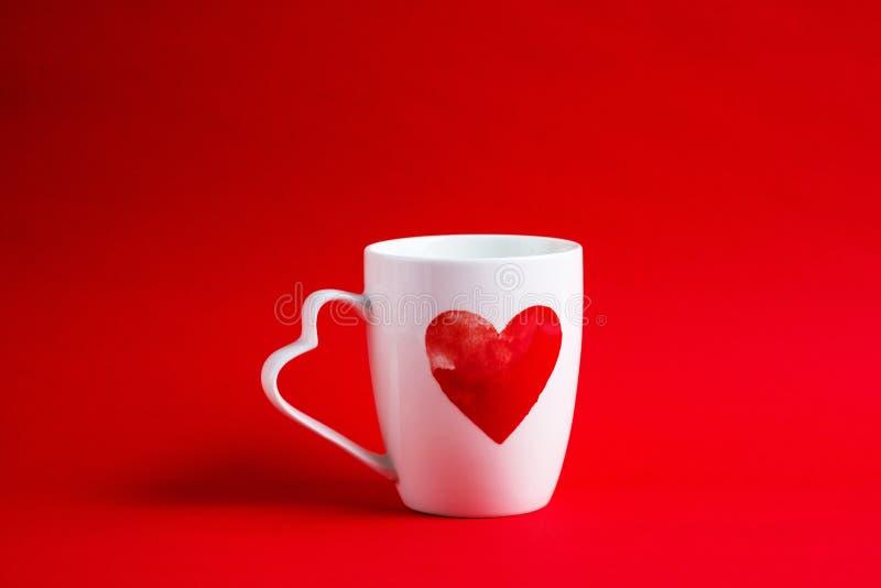 Biały kubek z sercem na czerwonym tle zdjęcie royalty free