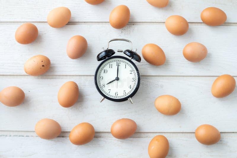 Biały kuchennego stołu tekstury tło z świeżymi jajkami ustawiającymi i klasyka zegarem zdjęcia royalty free