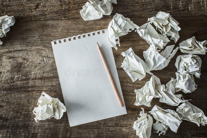 Biały kwadratowy papier, ołówek i marnotrawiący papiery na drewnianej plecy ziemi, zdjęcie stock