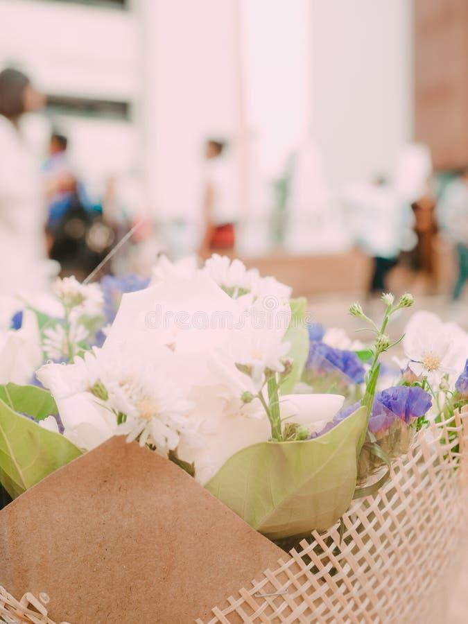 Biały kwiat i zieleń liść pakujemy w brown bukiecie z ludźmi półdupków obraz stock